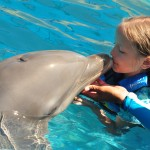 Girl kissing dolphins, Puerto Vallarta, Aquaventuras Park