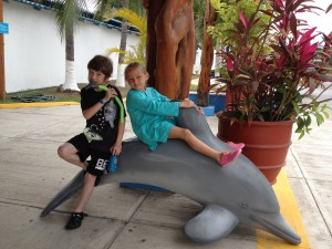 boy and girl sitting on dolphin statue