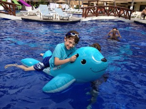 Boy riding floating blue seal raft in swimming pool