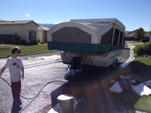 boy washes tent trailer with hose