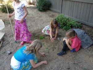 little girls planting a garden with weeds