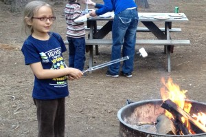 Little girl roasts marshmallows at campfire
