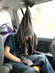Boy tries to sleep in car by hanging sweatshirt.