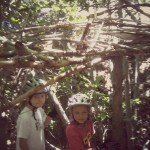 kids building fort in the forest out of wood and branches