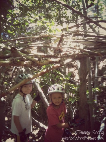 kids building fort in the forrest out of wood and branches