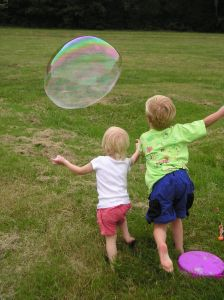Kids chase a bubble at a park